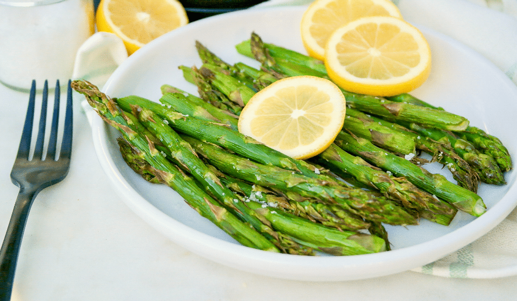 A white plate with cooked asparagus topped with bright yellow lemon slices.