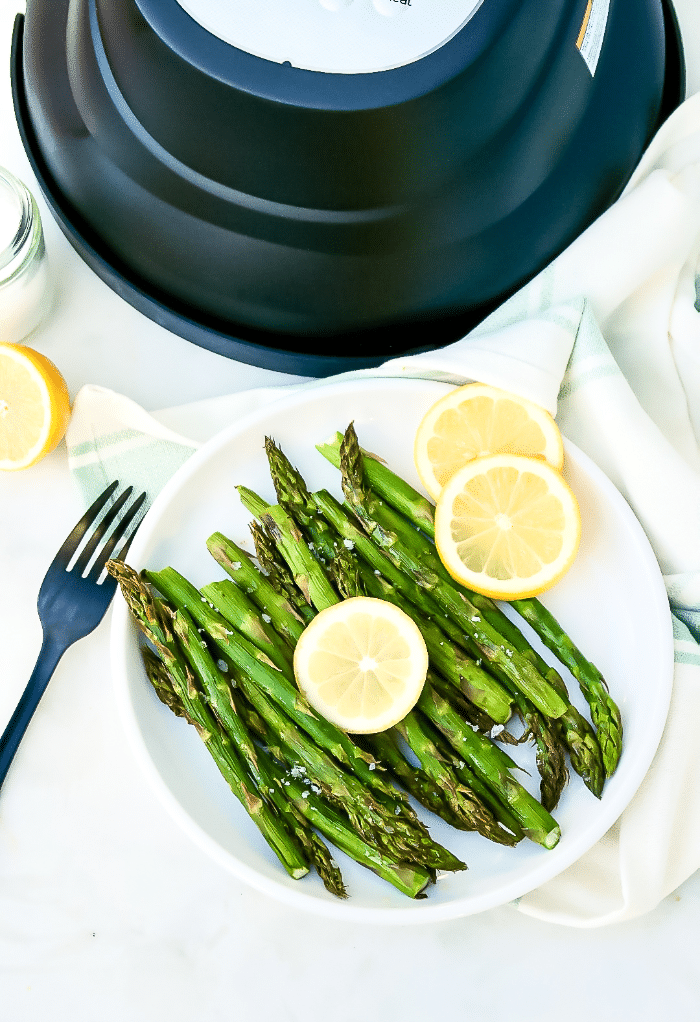 Top view of cooked asparagus on a white serving plate with a fork on the side of the dish.