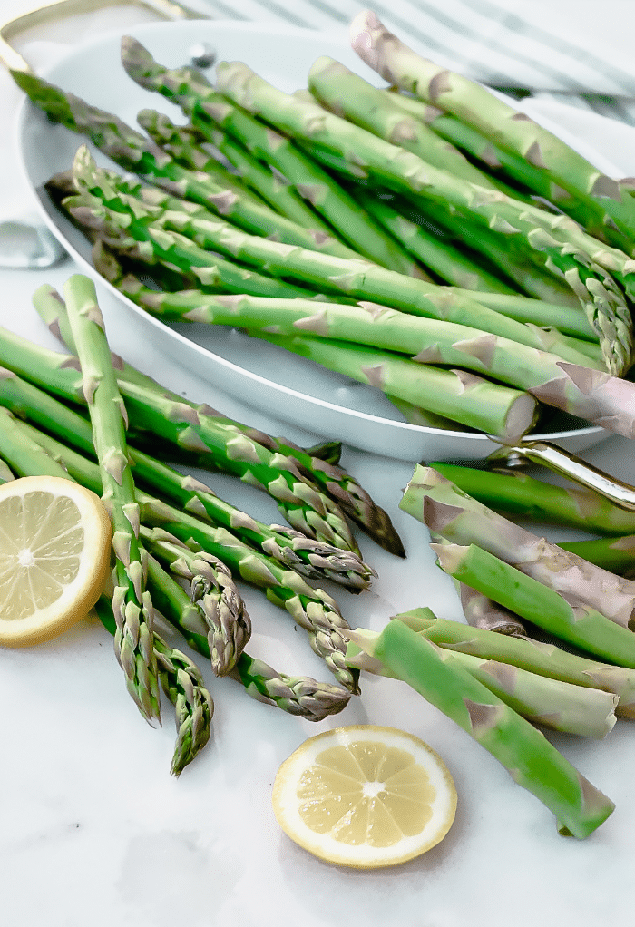 Fresh asparagus cleaned and sliced placed in a white serving platter.