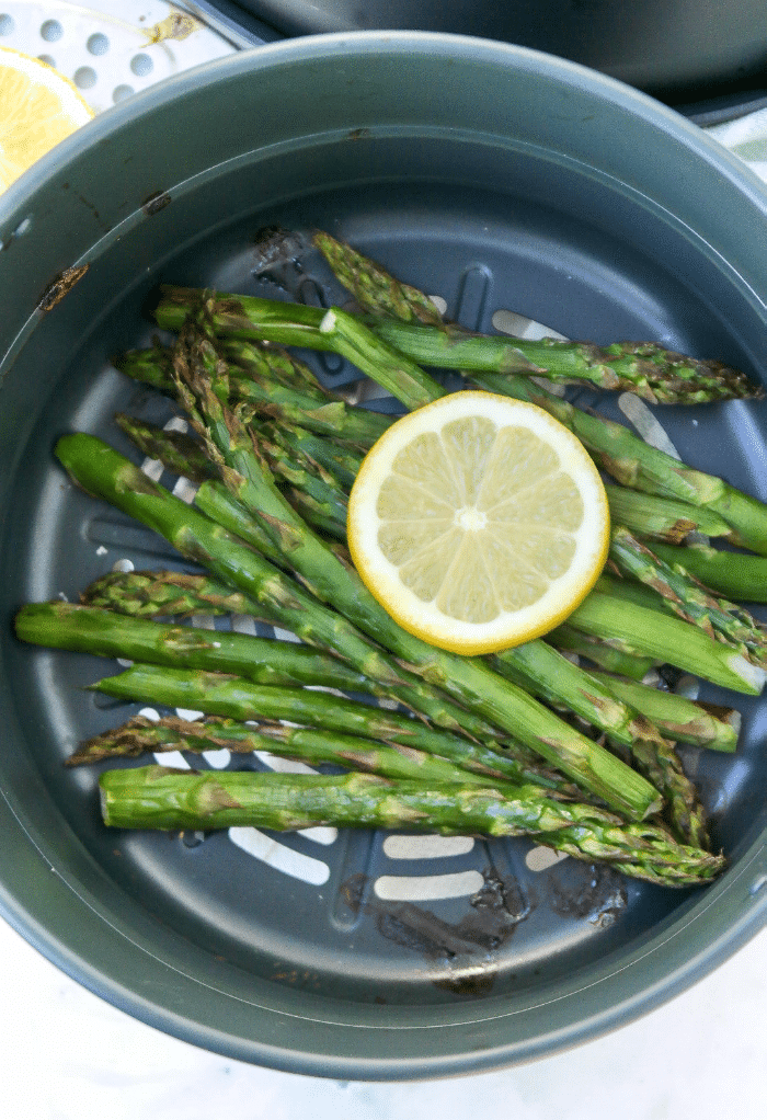 Cooked asparagus in an air fryer topped with a slice of lemon.