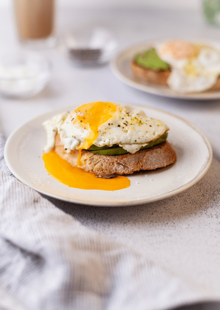 Sunny side up egg with the yolk oozing over avocado toast.