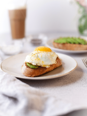 Avocado toast and egg on a white plate ready to eat