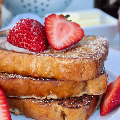 Three slices of Keto French toast topped with fresh strawberries cut in half.