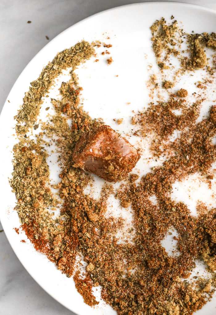 Pieces of pork rolled into spices before cooking in an Instant Pot.