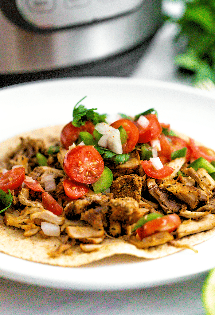 A close view of pork carnitas made in an instant pot on a white plate ready to eat.