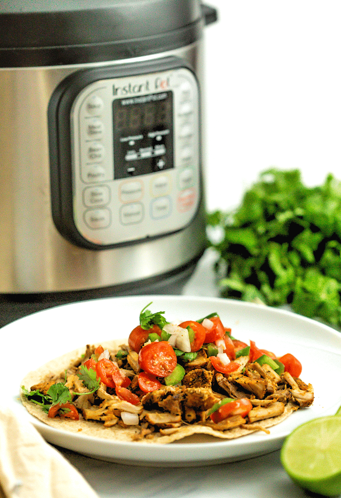 Instant Pot Carnitas on a white plate with an Instant Pot in the background.
