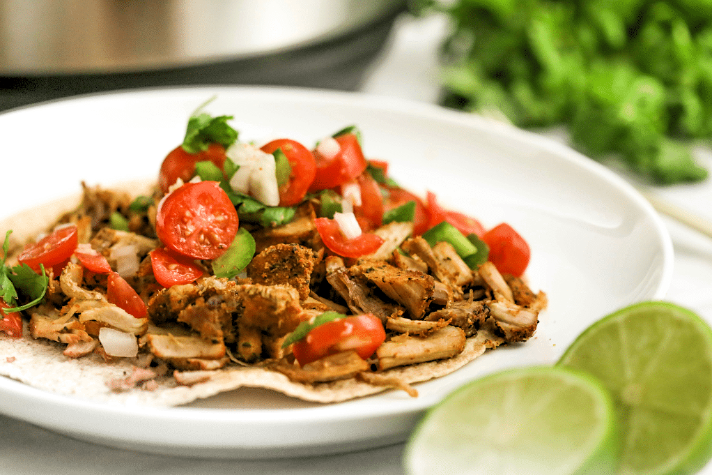 Pork carnitas on a white plate with fresh lime on the side.
