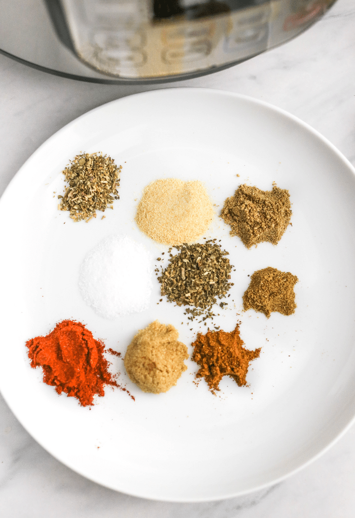 Spices on a white plate to be mixed together for carnitas.