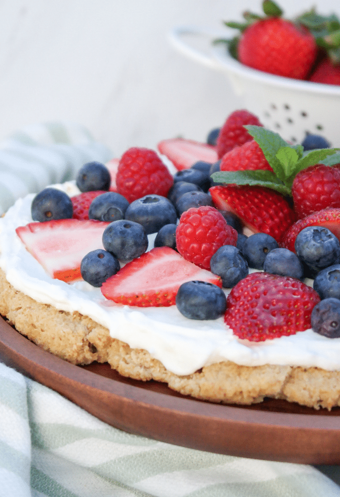A side view of half of a dessert pizza topped with fruit.
