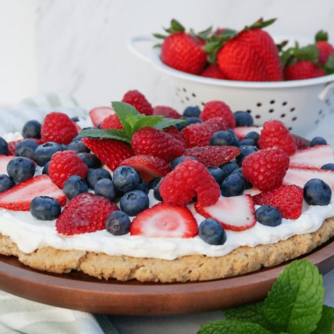 Dessert pizza topped with fresh berries over a whipped cream base.