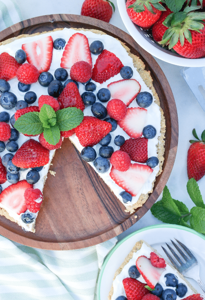 Keto fruit pizza on a wooden serving plate with berries along the side.