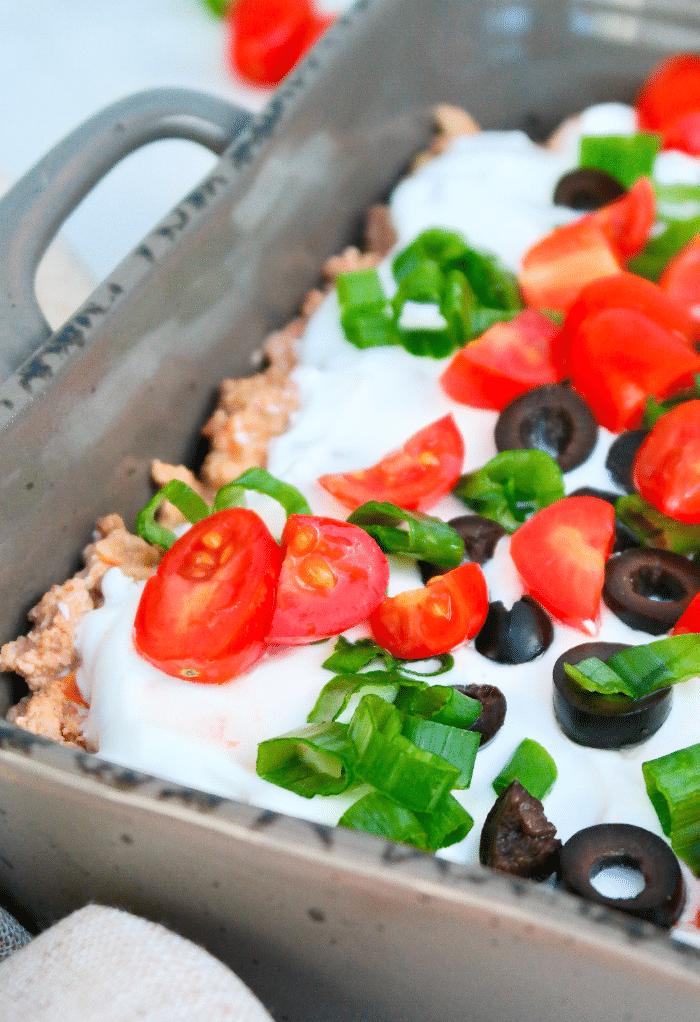 Ingredients layered on a casserole dish to make keto taco casserole.