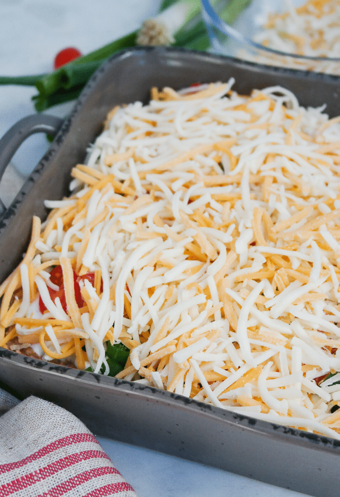 Shredded cheese on top of keto taco casserole before cooking.
