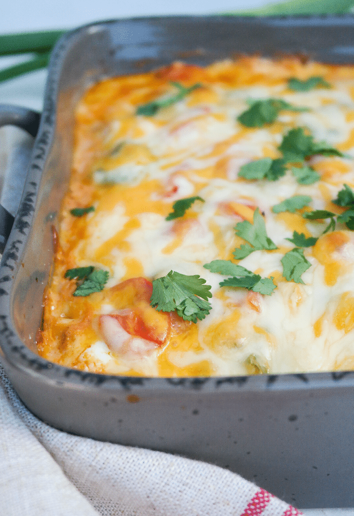 Casserole dish with melted cheese on top with fresh cilantro.