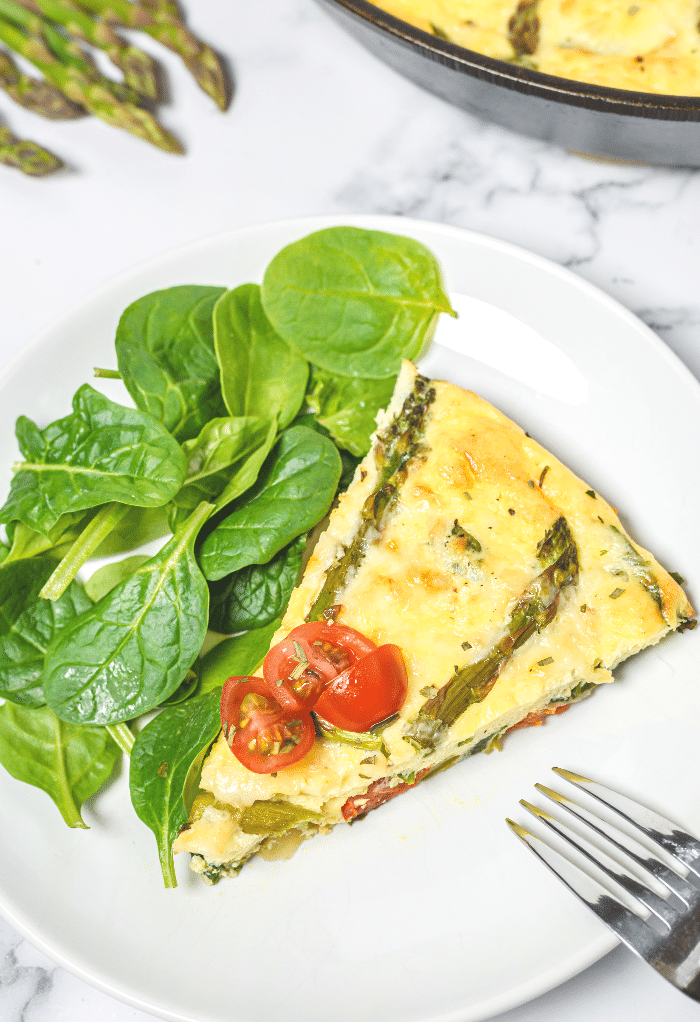 A slice of keto frittata with spinach salad ready to enjoy.