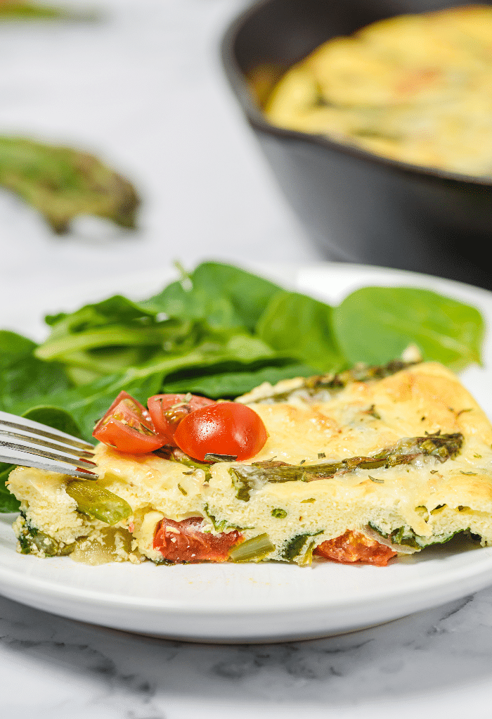 Slice of frittata with asparagus on a white plate.