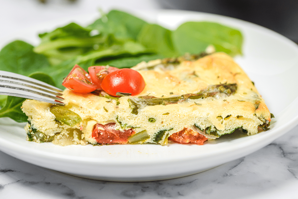 A slice of frittata with asparagus on a white plate.