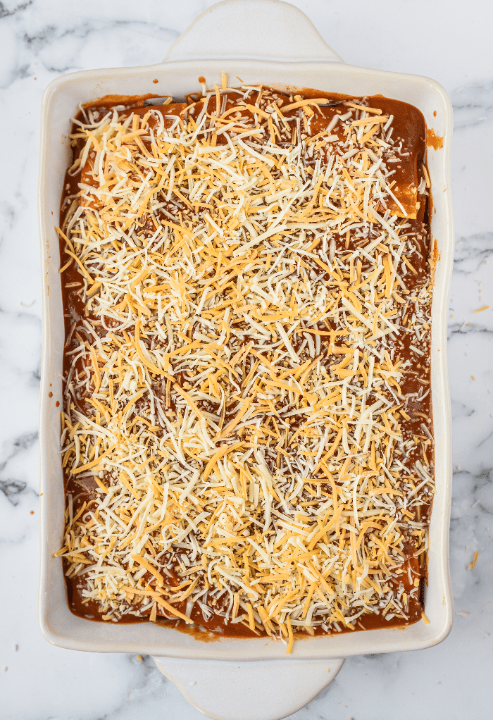 Cheese on top of enchilada sauce before baking.