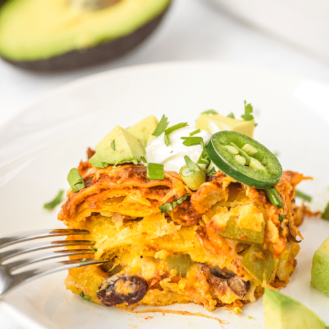 Slice of enchilada casserole topped with a slice of jalapeno and sour cream.