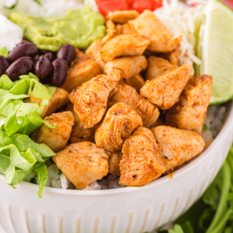 Chipotle chicken bowl with lettuce beans topped with lime.