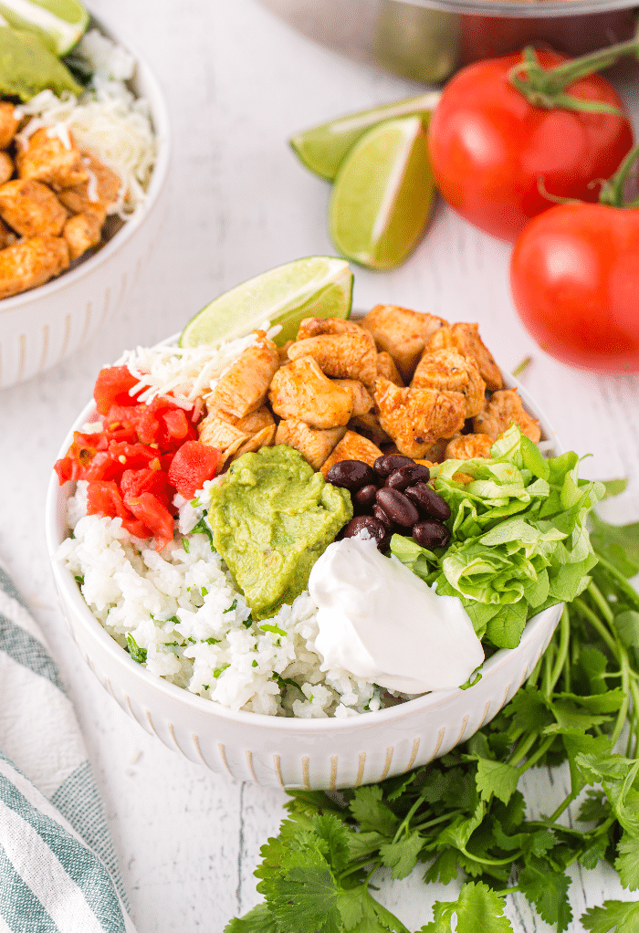 A chicken bowl with tomatoes, beans, rice and guacamole in a white bowl.