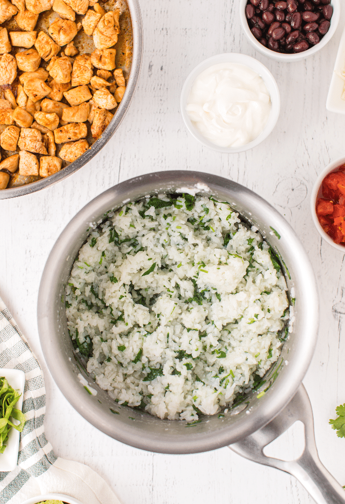 Cilantro mixed in white rice in a saucepan.