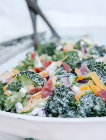 Classic broccoli salad in a white ceramic bowl.