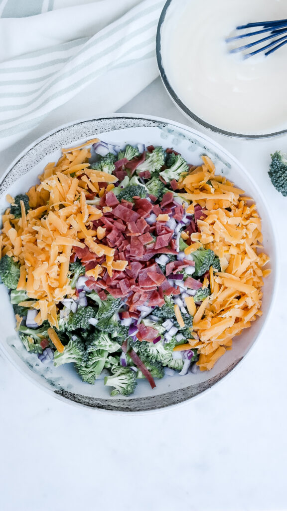 A large white bowl with broccoli, cheese, bacon to make a cold salad.