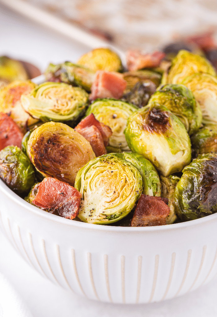 A white bowl filled with roasted Brussel sprouts with bacon.