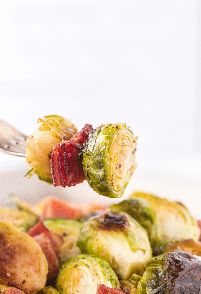A forkful of cooked bacon and Brussels sprouts.