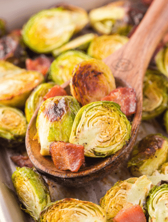 A wooden spoon full of roasted Brussels sprouts.