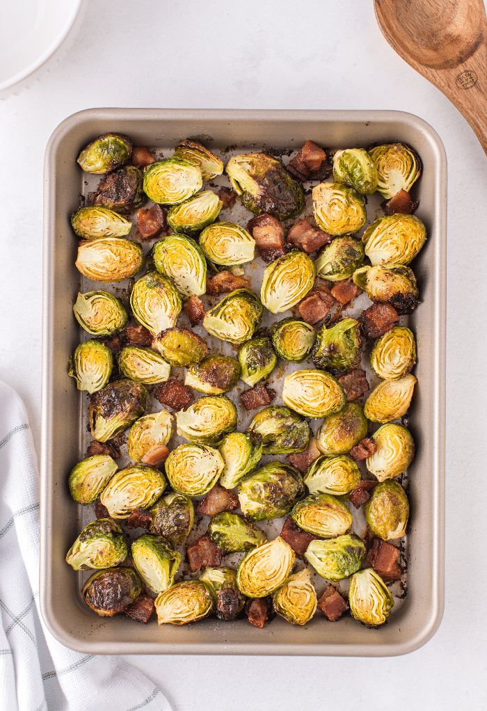 Cooked Brussels sprouts with bacon on a baking sheet.