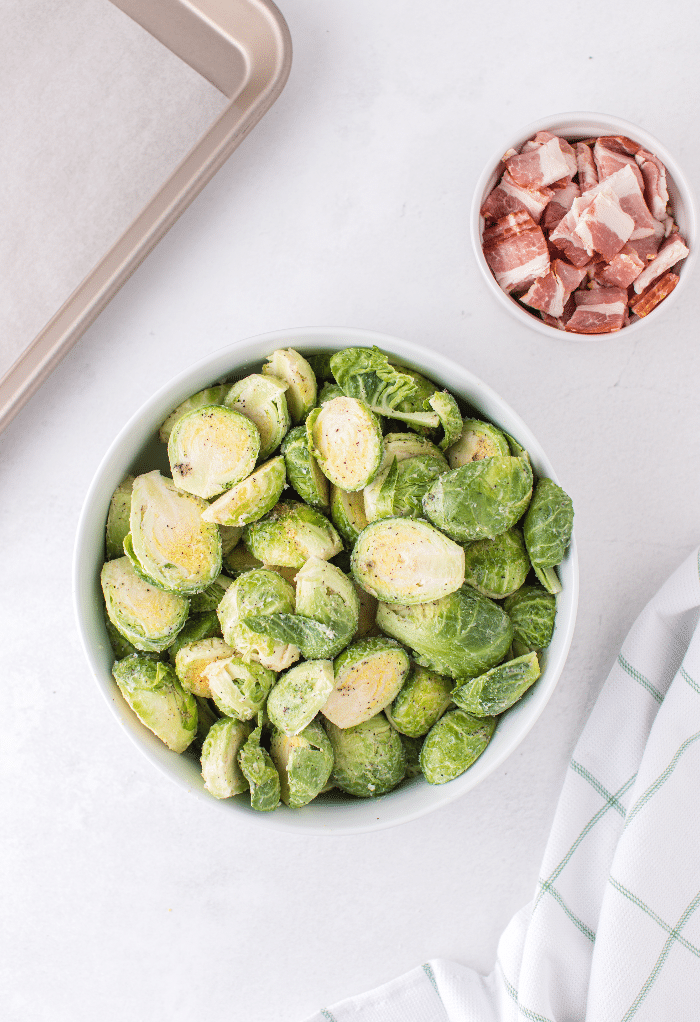 Diced bacon in a small bowl with clean and seasoned fresh Brussels sprouts ready to cook in the oven.