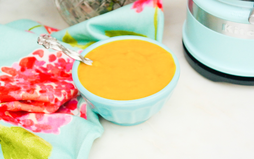 Homemade mango puree in a teal bowl ready to use.