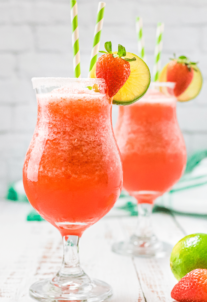 Two hurricane glasses with strawberry daiquiri topped with fresh fruit.