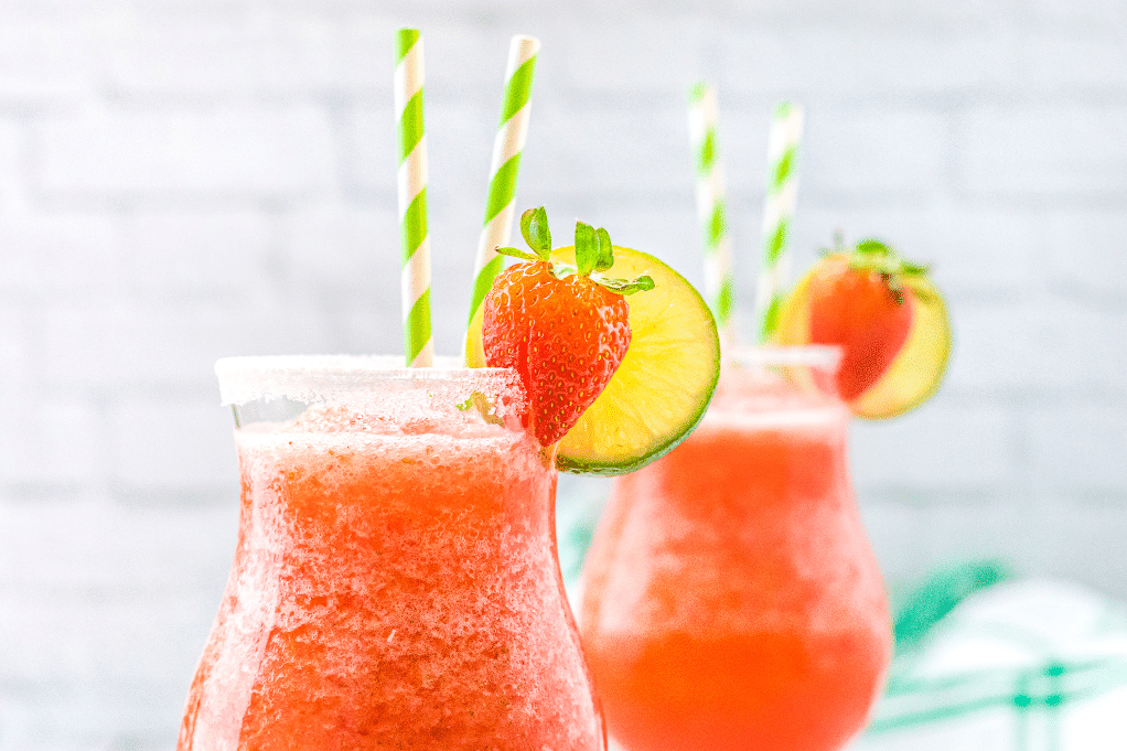 Close view of frozen strawberry daiquiri in clear glasses.