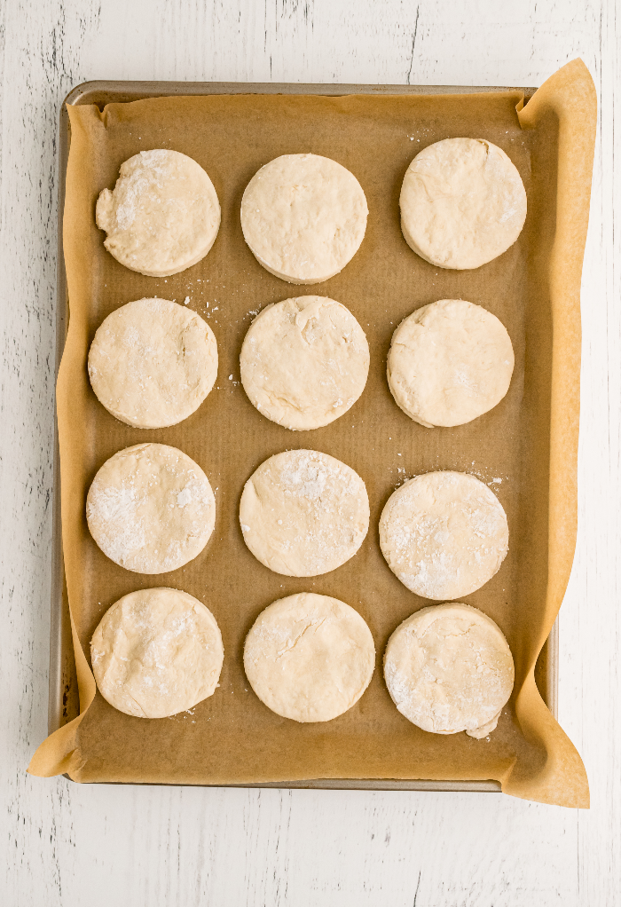 Unbaked biscuits on a baking sheet covered with brown parchment paper ready to bake.