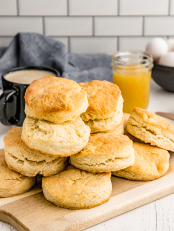 A dozen homemade buttermilk biscuits on a brown cutting board ready to enjoy.