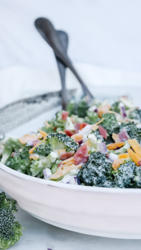 Keto broccoli salad with bacon in a white ceramic bowl with serving utensils ready to serve.