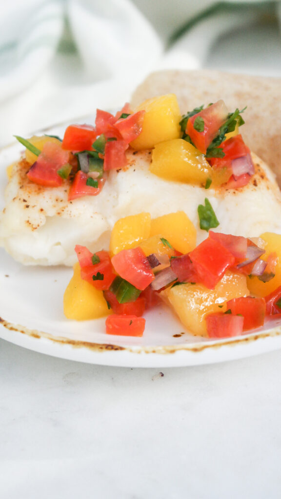 White cooked fish on a white plate topped with mango pico de gallo.