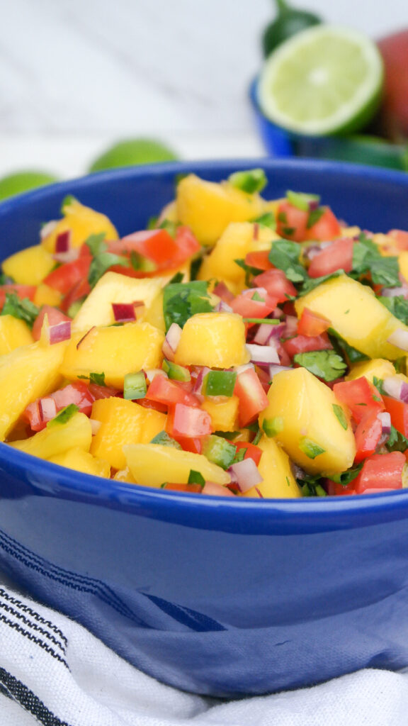 Fresh fruit salsa with mangos in a blue serving bow.