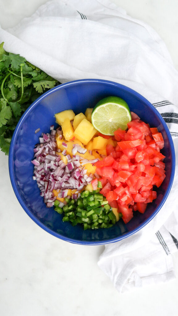 Ingredients to make a fruit pico de gallo in a blue serving bowl.