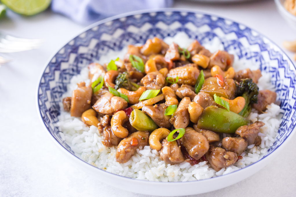 Teriyaki chicken with cashews in a white bowl with a blue rim.