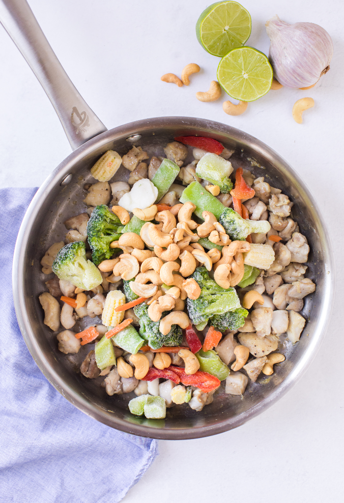 Vegetables with the chicken in a skillet.