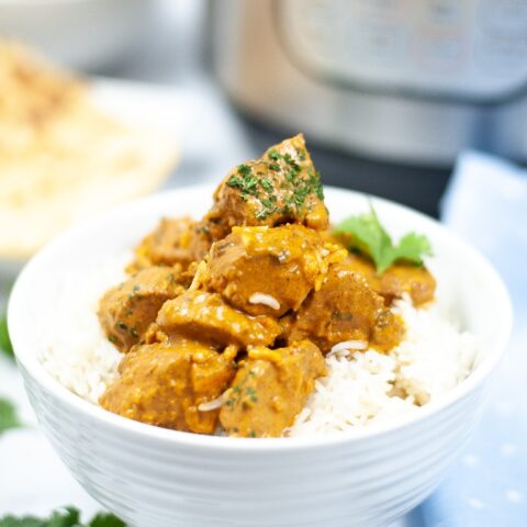 Butter chicken in a white bowl with rice.