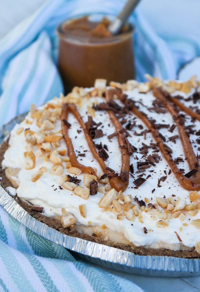 Peanut butter pie topped with a peanut drizzle and whipped cream.
