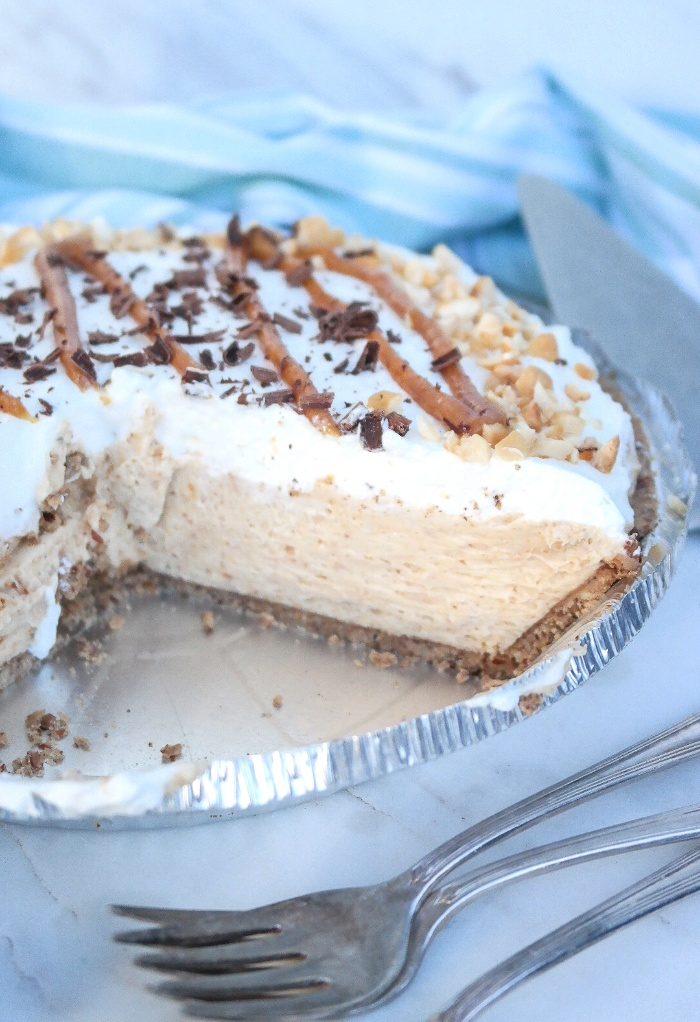 A peanut butter pie with a couple of slices taken out.