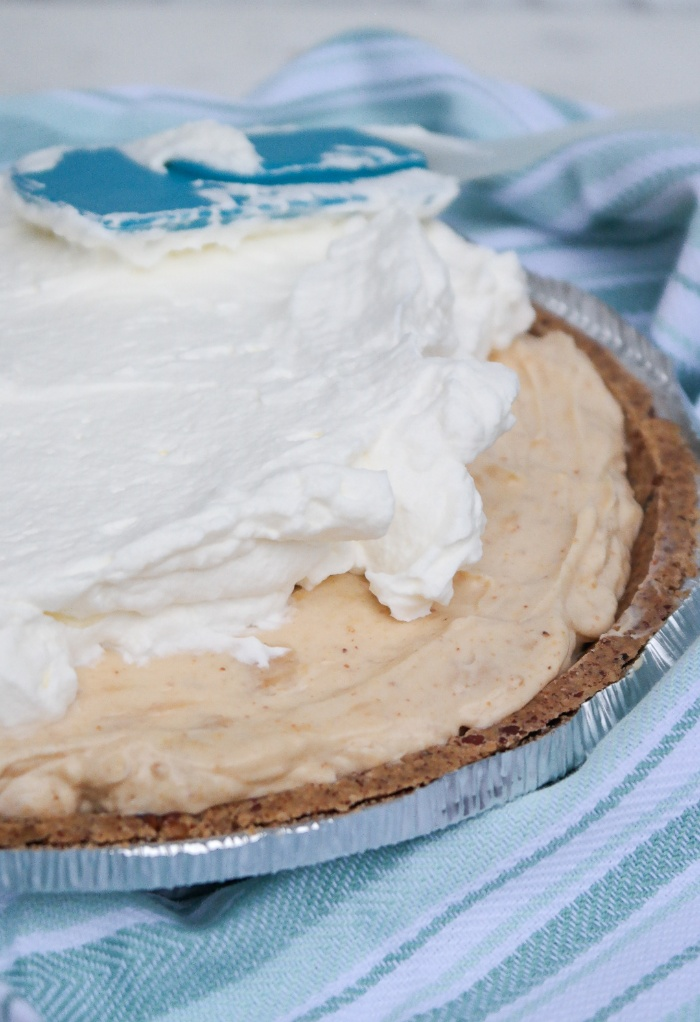 Fresh whipped cream over a peanut butter pie.