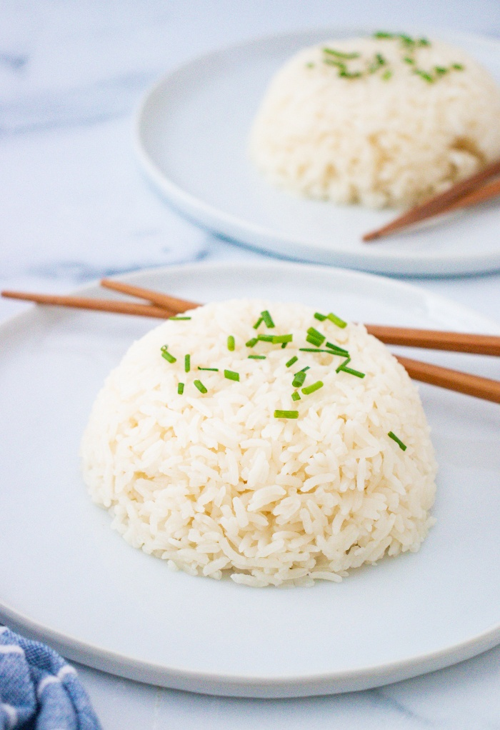 A plate with sticky rice with chopsticks on the side.