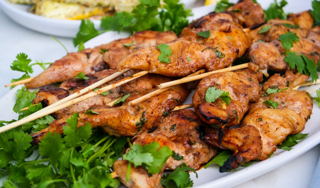 A white platter with chicken skewers.